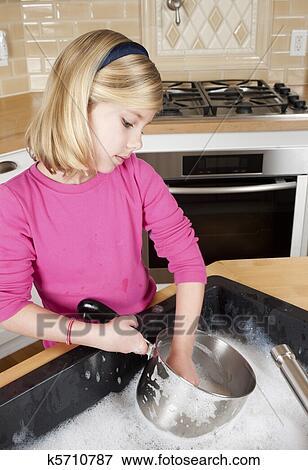 bild junges m dchen helfende mit putzen per w sche dishes m dchen halten kochen. Black Bedroom Furniture Sets. Home Design Ideas