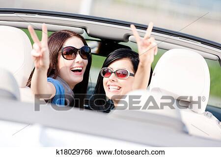 stock bilder zwei m dchen sitzen auto und gesturing siegeszeichen k18029766 suche. Black Bedroom Furniture Sets. Home Design Ideas