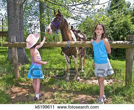 stock fotografie zwei m dchen und a pferd k6199611 suche stockfotos fotos prints. Black Bedroom Furniture Sets. Home Design Ideas