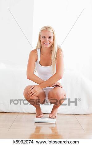 фото женщины сидящей на корточках в белых трусах
