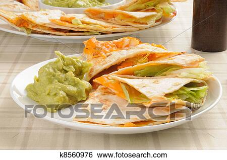plate of cheddar cheese quesadillas with guacamole dip