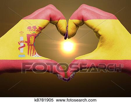 Gesture made by spain flag colored hands showing symbol of heart and