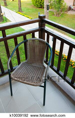 Stock photo of wicker chair on the balcony k10039192 - searc.