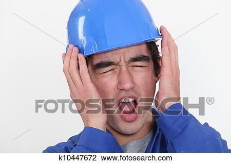 Stock Photo of A young manual worker hearing unbearable ...