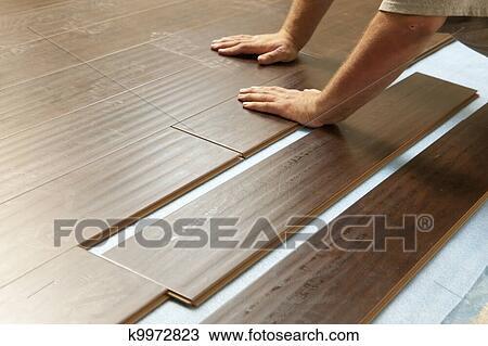 stock foto mann installieren neu laminat holz fussboden k9972823 suche stock. Black Bedroom Furniture Sets. Home Design Ideas