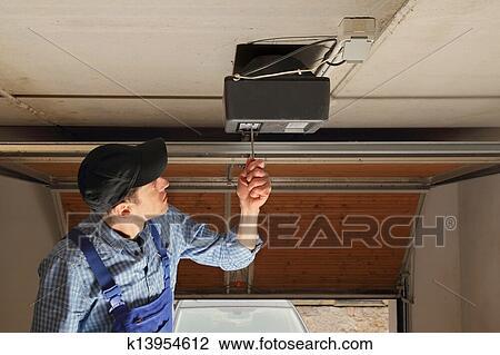 stock foto handwerker installieren a elektrisch garagentorantrieb k13954612 suche. Black Bedroom Furniture Sets. Home Design Ideas