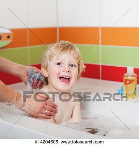 stock image of boy sitting in tub while mother bathing him k