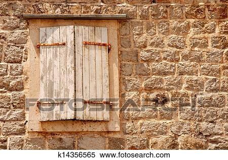 stock image of window with shutters in old wall
