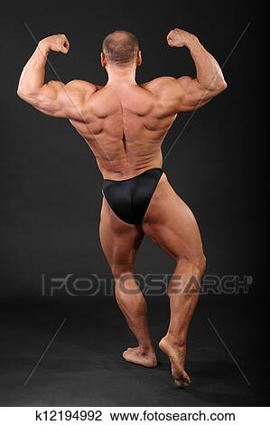 Stock Photo Of Undressed Bronzed Bodybuilder Shows The Muscles