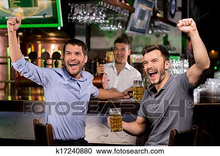 stock photography of watching tv in bar two happy young men stock photography watching tv in bar two happy young men drinking beer and gesturing