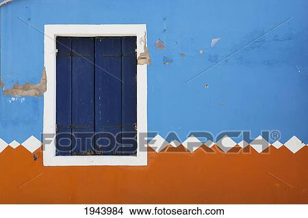 Stock photo of paint peeling off of a decorative exterior wall and a closed shutters on a window - Exterior paint peeling concept ...