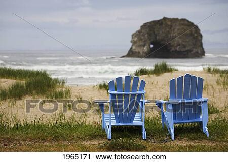 Stock Photography of two blue adirondack chairs on a grassy beach