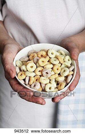 Stock Photo of Hands holding a bowl of multi-grain cereal loops ...