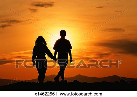 silhouette of couple holding hands in front of mountain sunset