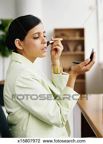 Stock Photo of Young woman holding mirror applying make up side