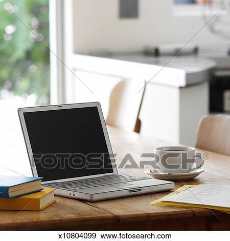 stock photograph of close up of a laptop on a kitchen table with a