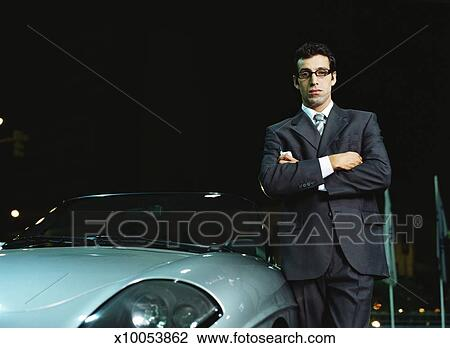 Stock Photo   Young Man In Suit Standing Beside Sports Car, Arms Crossed,  Night