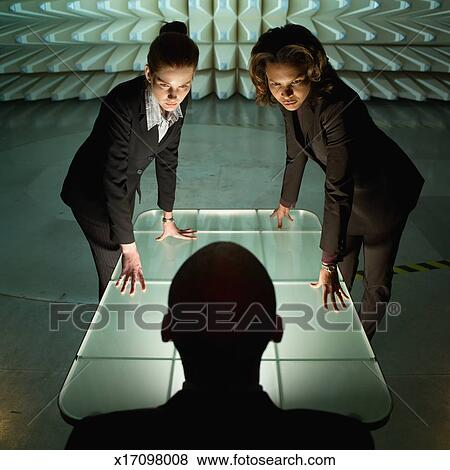 Pictures Of Two Women Leaning On Table Looking Down At Man