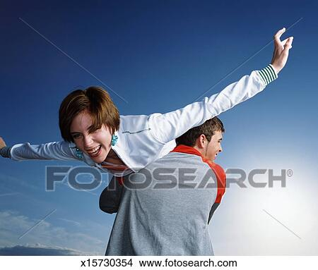 Of young man carrying young woman over his shoulder x15730354 search