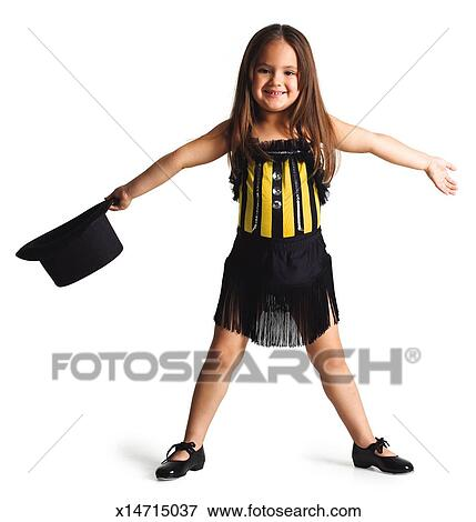 little ethnic girl in a dance outfit spreads her arms out and smiles ...