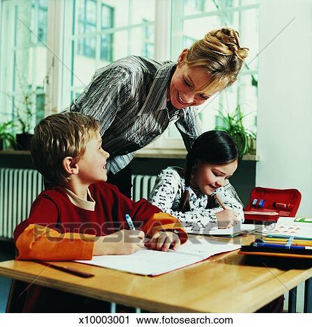 banques de photographies prof s 39 appuyer a bureau portion cole primaire enfants crire. Black Bedroom Furniture Sets. Home Design Ideas