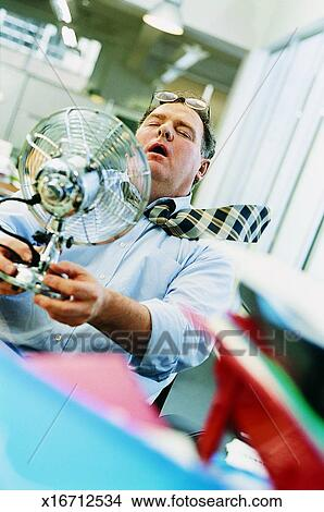 Stock Photo of Businessman in a Hot Office Holding an Electric Fan