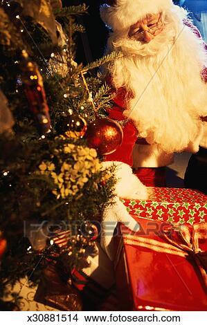santa claus putting presents under tree - Santa Claus With Presents