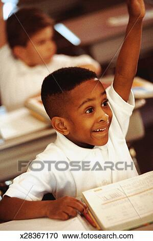 Stock Photography of Boy sitting at desk in classroom ...