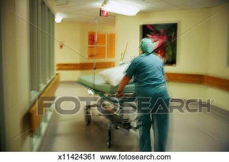 Stock Photography Of Hospital Orderly Pushing Empty Stretcher Down