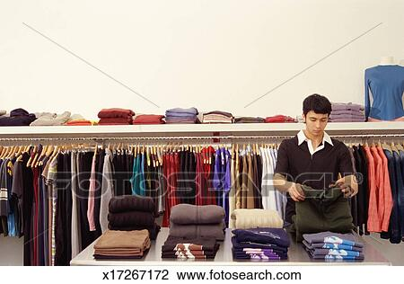 Stock Photo - Young woman buying clothes in a sale, Fat face clothing store, Norwich UK