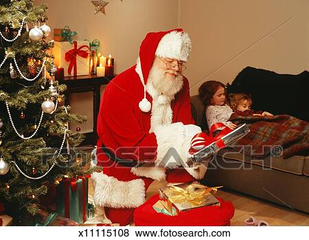 picture santa claus putting presents under christmas tree fotosearch search stock photos - Santa Claus Presents