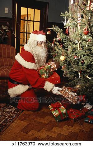 santa claus placing presents under christmas tree in living room - Santa Claus With Presents