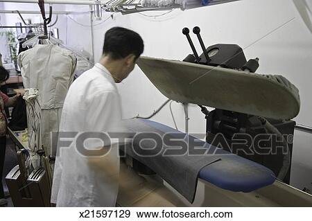 man pressing trousers in laundry presser laundry presser