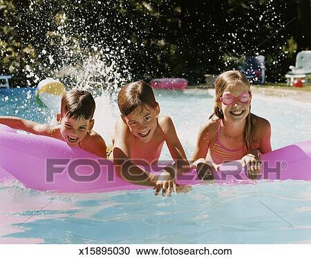banques de photographies trois enfants dans a piscine jouer une matelas pneumatique. Black Bedroom Furniture Sets. Home Design Ideas