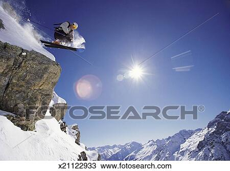 Stock Photo Of Skiier Jumps From Rock Face Of Mountain