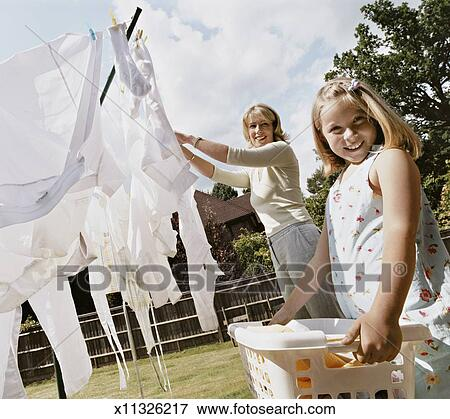 Picture Of Daughter Helping Her Mother To Hang Up Laundry