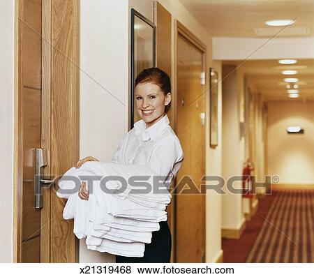 images femme chambre sourires comme elle livre pli serviettes dans a couloir h tel. Black Bedroom Furniture Sets. Home Design Ideas