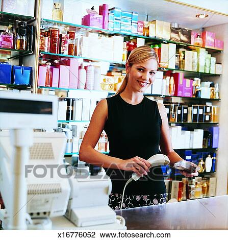 stock images of shop assistant checking a sales price tag on    shop assistant scanning perfume at cash register