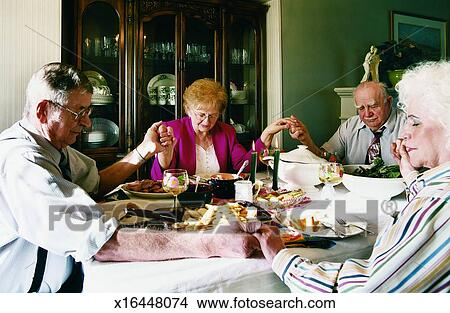 Stock Photo Of Four Elderly People Sit Holding Hands