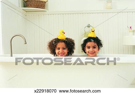 Stock fotografie portr t von schwestern in dass bad mit badeenten auf ihr k pfe - Foto in een bad ...