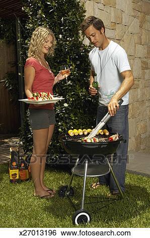 banque d 39 images jeune homme cuisine sur barbecue tenue femme plateau de kebabs et. Black Bedroom Furniture Sets. Home Design Ideas