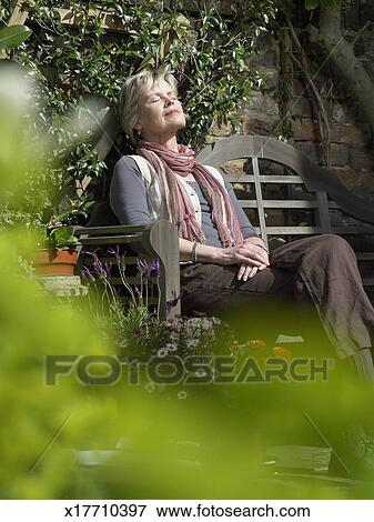 Picture Of Mature Woman Sitting On Garden Bench Resting