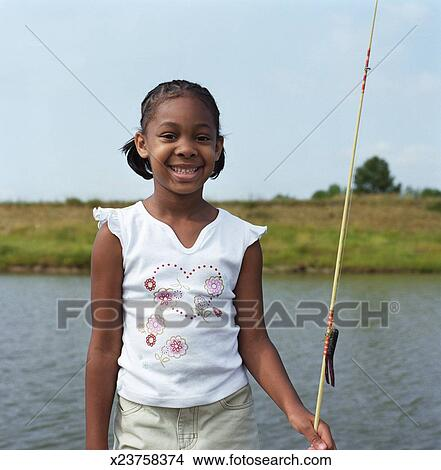 Stock photo of girl 5 7 standing beside waterway holding for Girl fishing pole