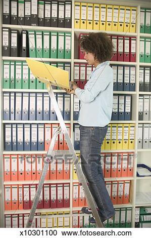 Banques de photographies jeune femme classement dans - Classement des dossiers dans un bureau ...