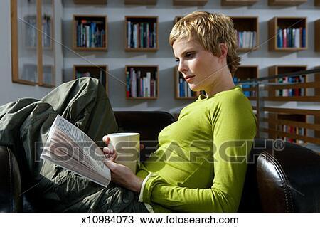 Stock foto frau lesen buch in sessel seitenansicht for Sessel lesen