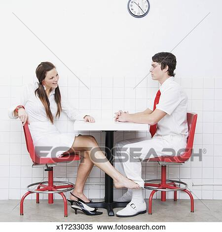 stock image of young couple sitting at table woman touching man 39 s leg with foot x17233035. Black Bedroom Furniture Sets. Home Design Ideas