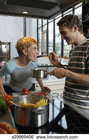 banque d 39 images couple dans cuisine cuisine homme tenue cuill re bois femme bouche. Black Bedroom Furniture Sets. Home Design Ideas