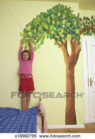 stock bild m dchen 4 6 stehen bett oben erreichen gegen baum malen auf wand. Black Bedroom Furniture Sets. Home Design Ideas