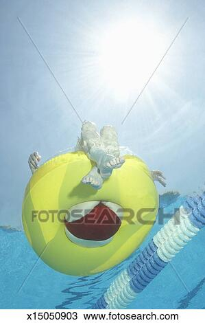 Stock Photo of Senior woman sitting in rubber ring in swimming pool ...