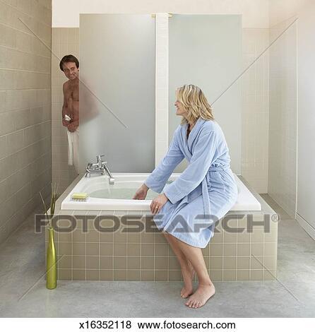 bilder frau f llen badewanne mit wasser mann stehen in dusche in hintergrund. Black Bedroom Furniture Sets. Home Design Ideas